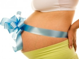 34 weeks pregnant belly with a blue bow against a white background
